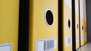 A shelf with documents in storage bins